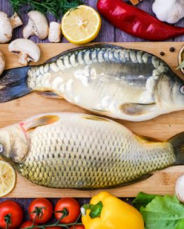 carp-mirror-carp-cutting-board-surrounded-by-vegetables-fresh-fish-before-cooking-with-vegetables_131638-168